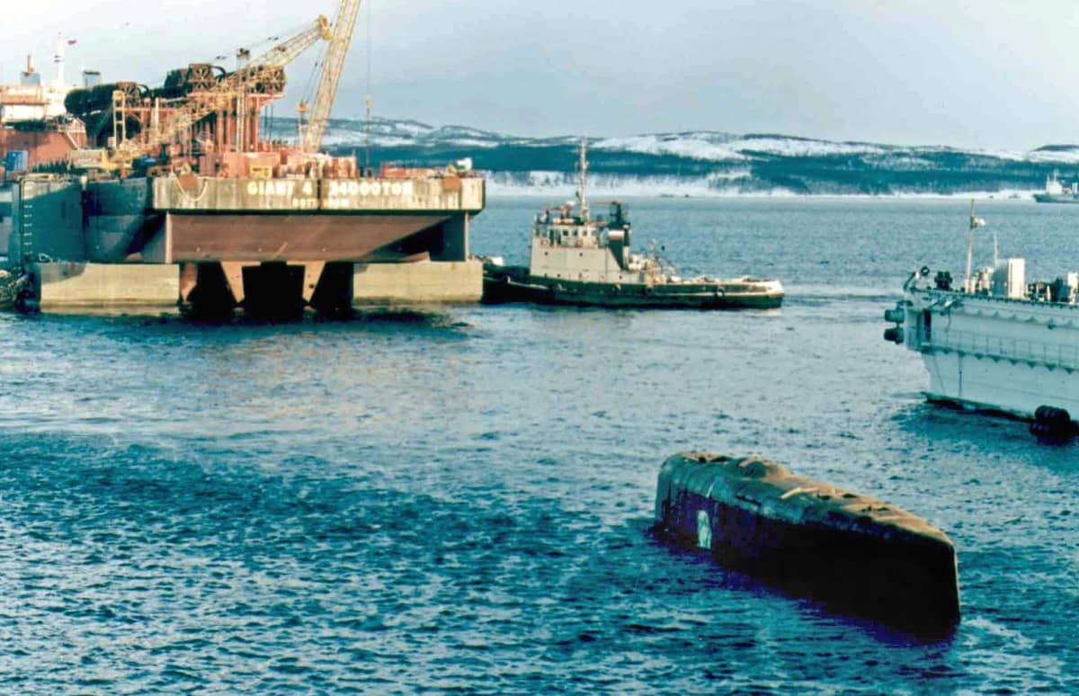 Sukellusvene Kurskin nosto-operaatio Venäjällä 2001. The conning tower (bottom right) of the Kursk nuclear submarine appears on the water surface at a dock at the port of Roslyakovo, near Murmansk, 23 October 2001. The Kursk nuclear submarine surfaced for the first time on Wednesday, 23 October 2001, some 14 months after a number of still-unexplained explosions sank the vessel with 118 men on board. EPA PHOTO EPA POOL/STRINGER