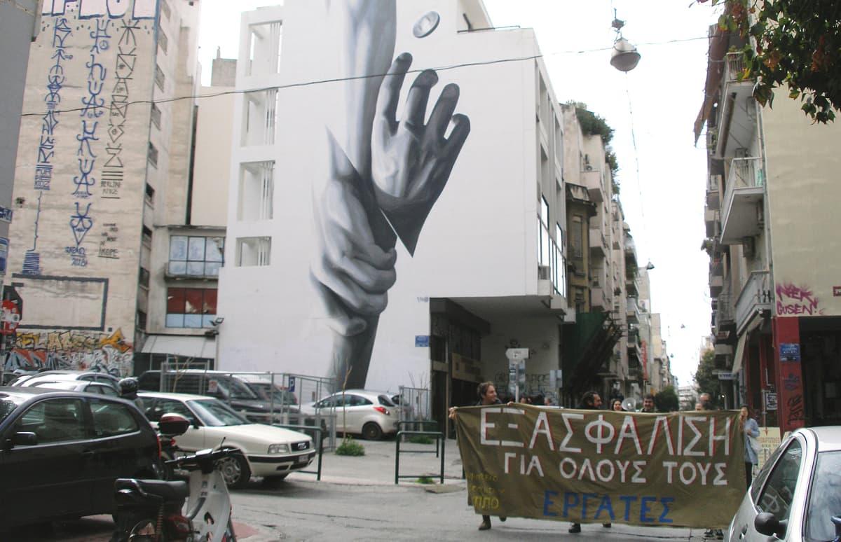 Katutaiteilija iNO:n muraali vetää kreikkalaisia ylös vaikeuksista. Mielenosoitusbanderollissa vaaditaan oikeuksia kaikille työläisille.