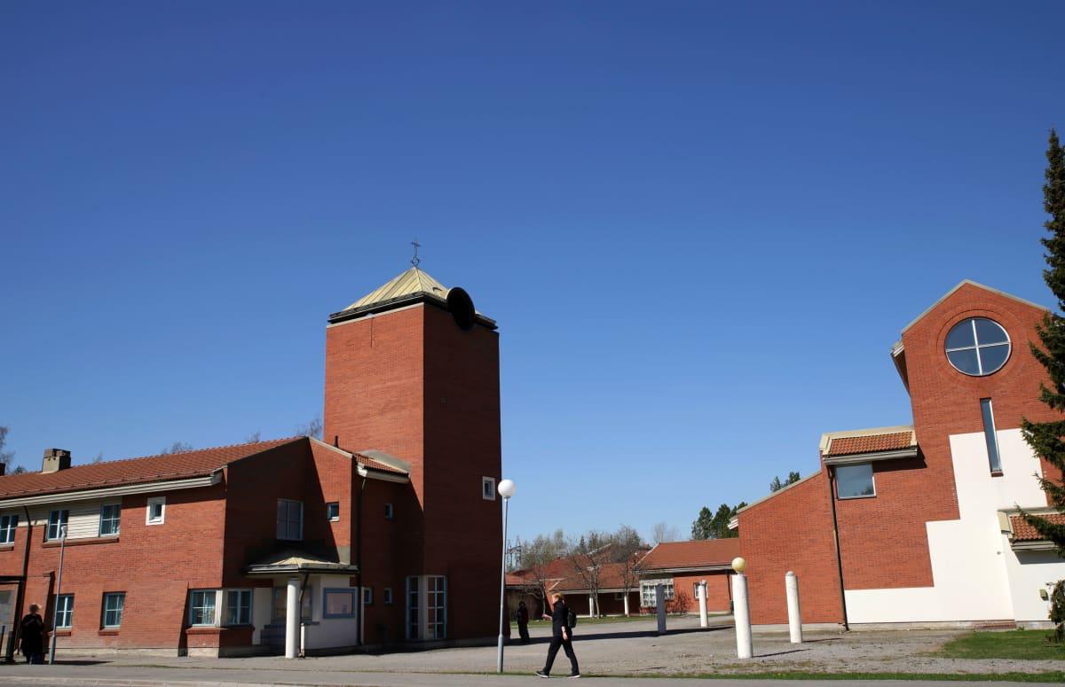 Kuvassa näkyy kaksi punatiilistä Huhrtasuon seurakuntakeskuksen rakennusta. Molemmissa on tornimainen pääty.