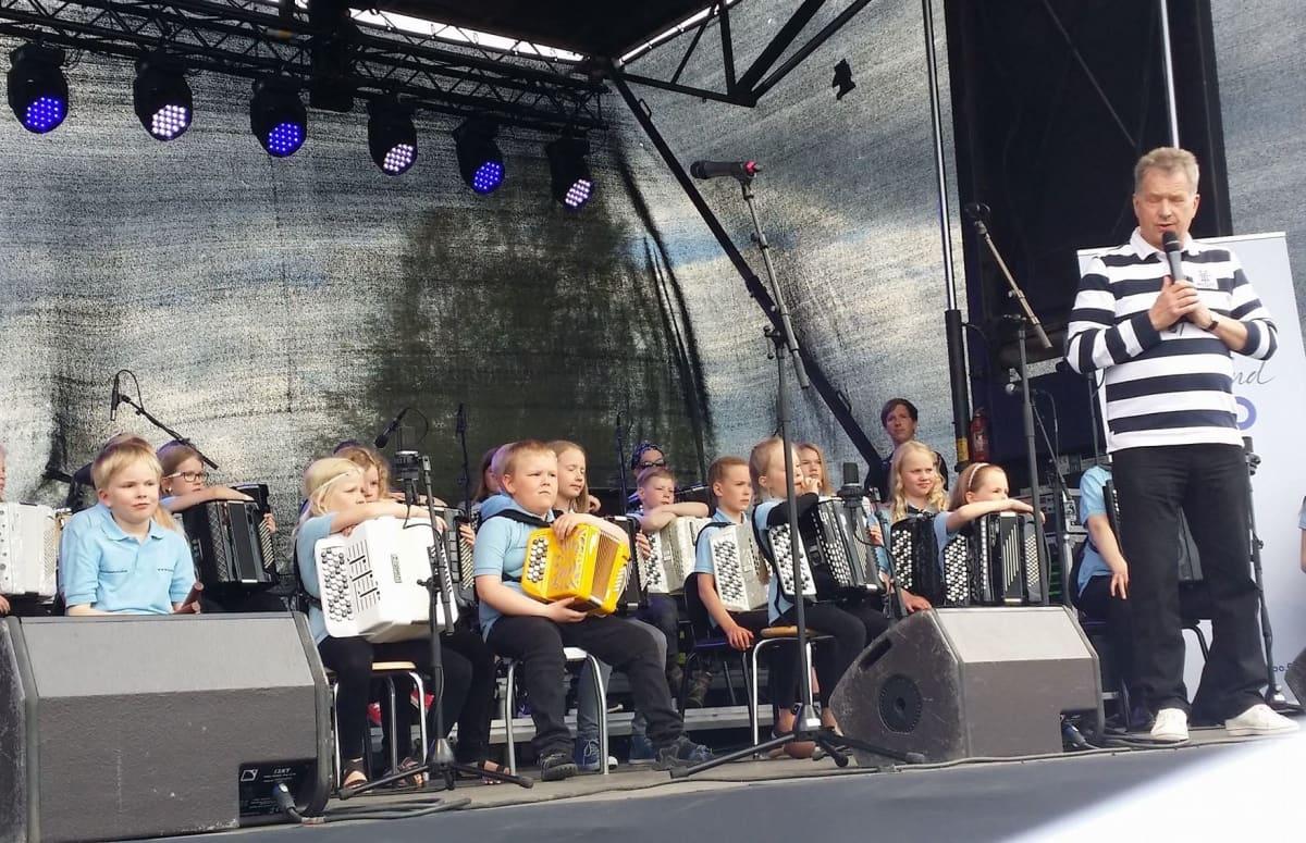Presidentti Sauli Niinistö puhuu Kokkolan Meripuistossa, taustalla Kokkolan Junioriharmonikat.