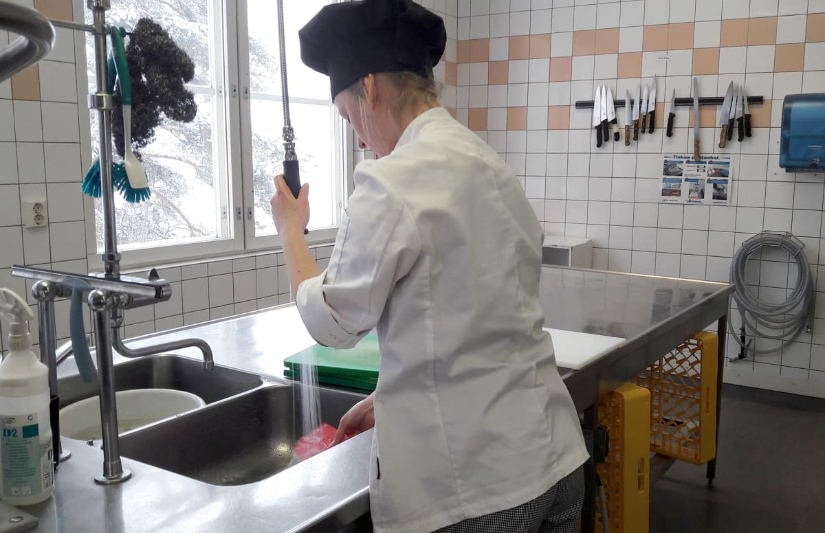 Kokkiopiskelija tiskaa astioita koulussa.