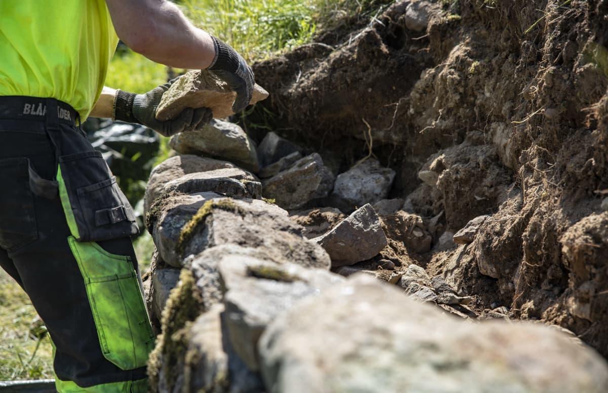 Työmies korjaamassa Kärnäkosken linnoituksen vallia.