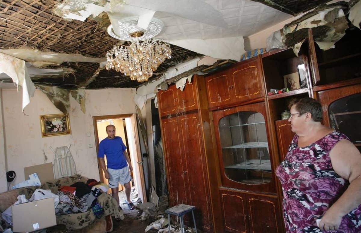 Asukkaat tutkivat pommituksen aiheuttamia vaurioita kodissaan Donetskissa 2. elokuuta.