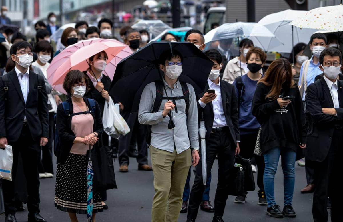 Ihmisiä katukäytävällä rinta rinnan. Kaikilla on maskit. Osa kantaa sateenvarjoa.