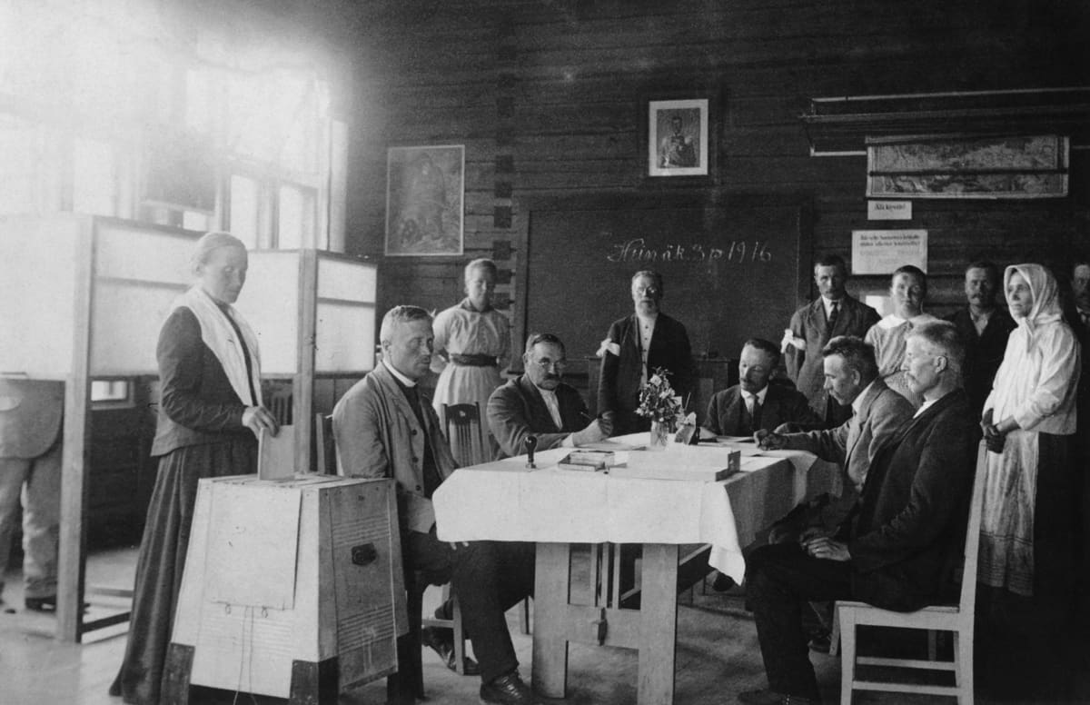 Vaalitoimitsijoita. Äänestäjä pudottaa äänestyslippuaan vaaliuurnaan Hauhon koululla eduskuntavaaleissa 1916.