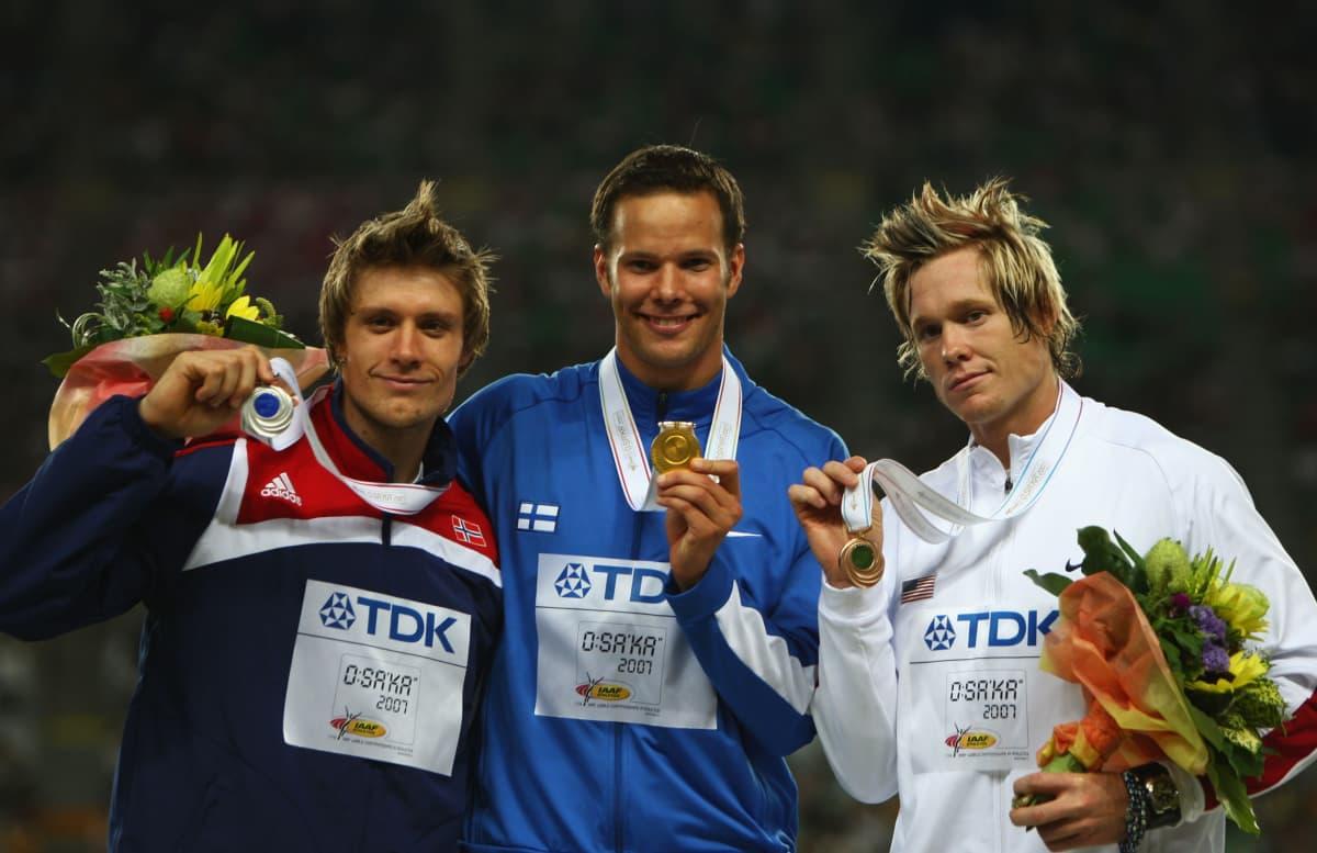 Andreas Thorkildsen, Tero Pitkämäki ja Breaux Greer poseerasivat mitalien kanssa vuoden 2007 MM-finaalin jälkeen. Kolmikosta vain Greer joutui urallaan olkapääleikkaukseen.
