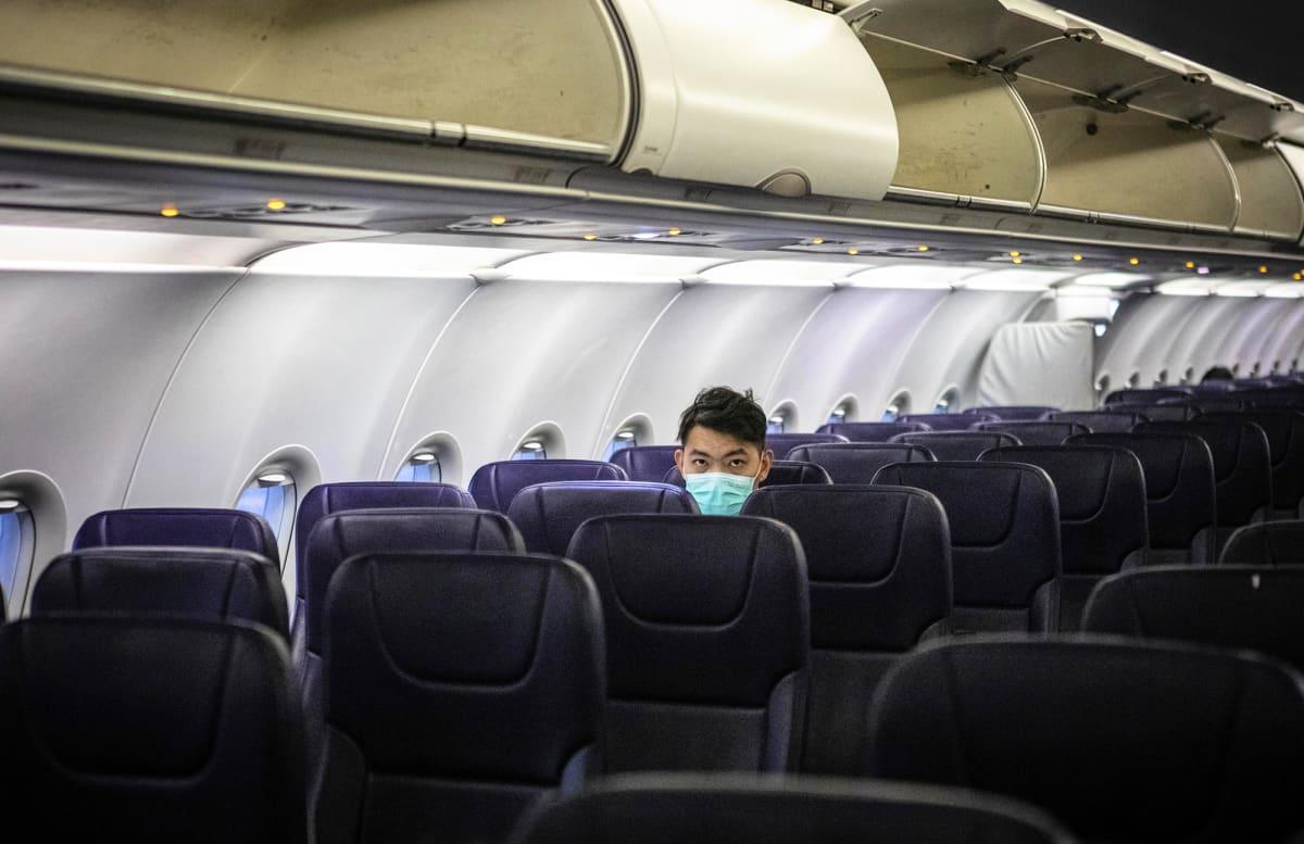 Hengityssuojaimeen pukeutunut matkustaja istuu tyhjässä lentokoneen matkustamossa.