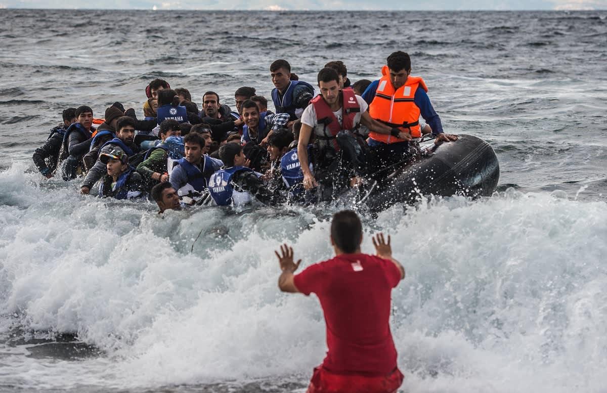 Punapaitainen mies seisoo meren aalloissa kädet eteen ojennettuna, aaltoihin on juuri tippumassa ihmisiä pelastusveneestä joka on ääriään myöten täynnä.