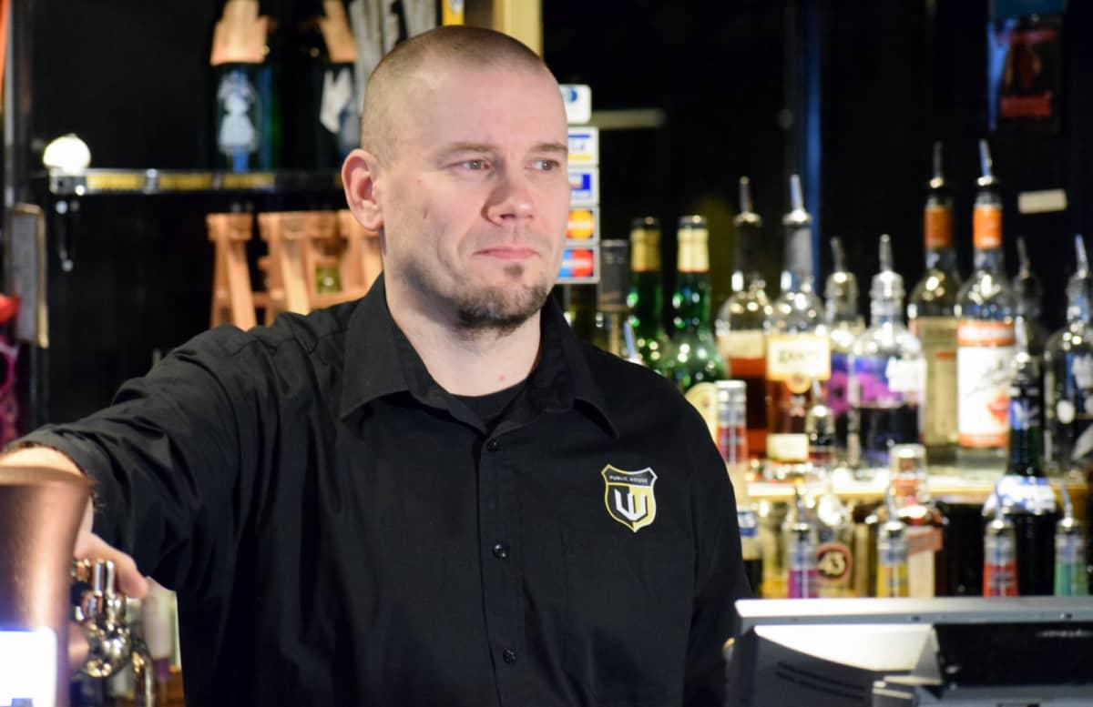 Ravintolapäällikkö Juha Marttinen baaritiskin takana.