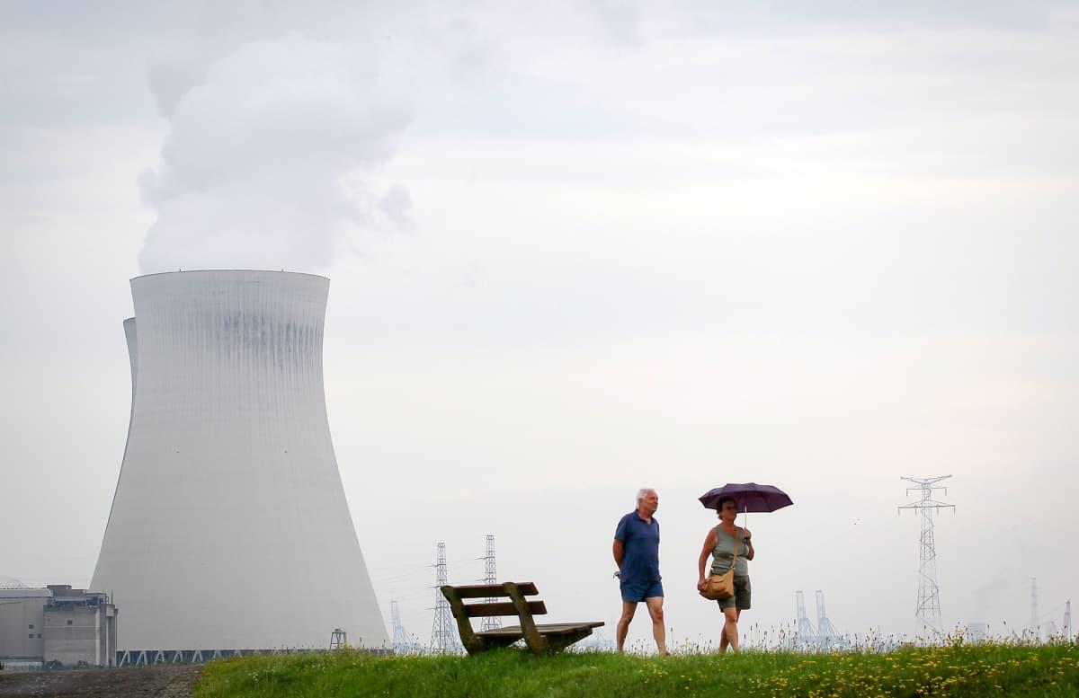 Pariskunta kävelee Doelin ydinvoimalan vieressä.