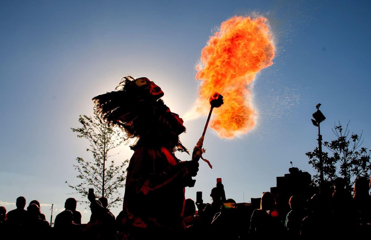 Tulitaiteilija pukeutuneena perinteiseen asuun sylkien tulta suustaan.