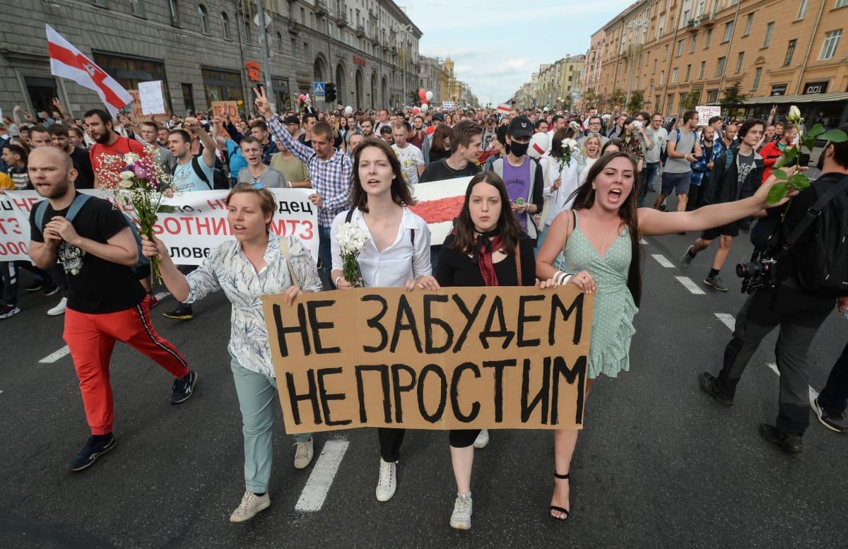 """Mielenosoittajat marssivat Minskin kaduilla perjantai-iltana. Kyltissä lukee: """"Emme unohda, emme anna anteeksi""""."""