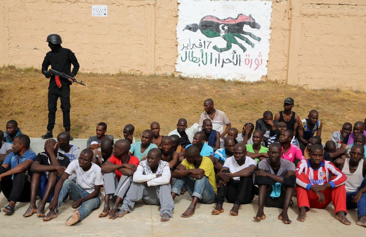 Kymmeniä miehiä istuu maassa, yksi mies seisoo mustissa vaatteisia ase kädessä.