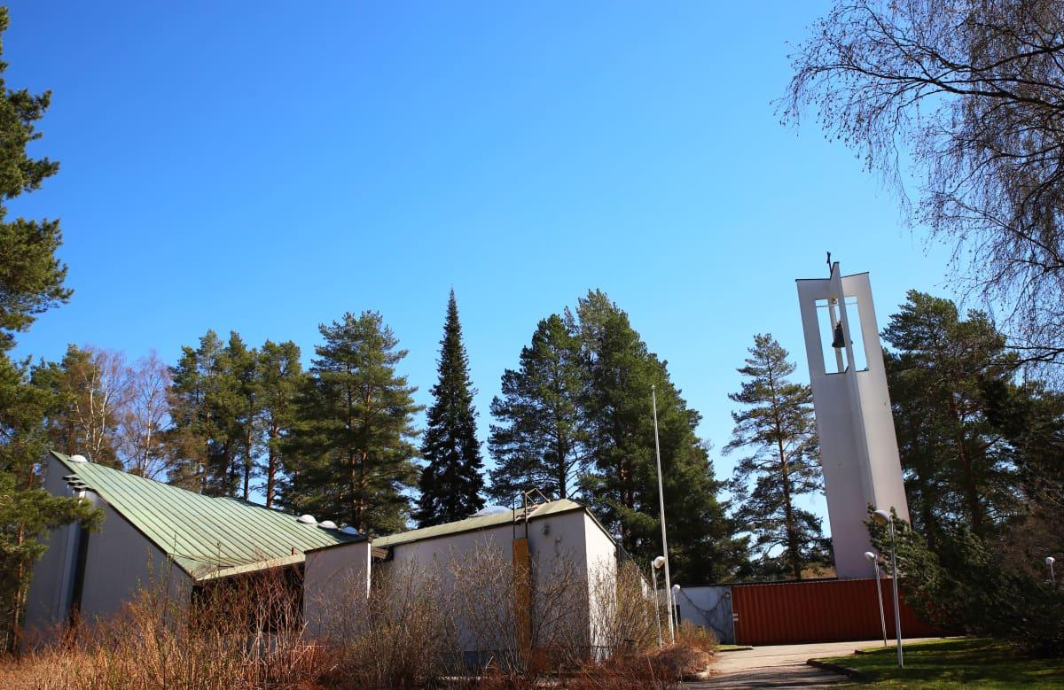 Kuvassa näkyy valkoseinäinen ja vihreäkattoinen Lohikosken seurakuntakeskus sekä avoin ja pelkistetty kellotorni.