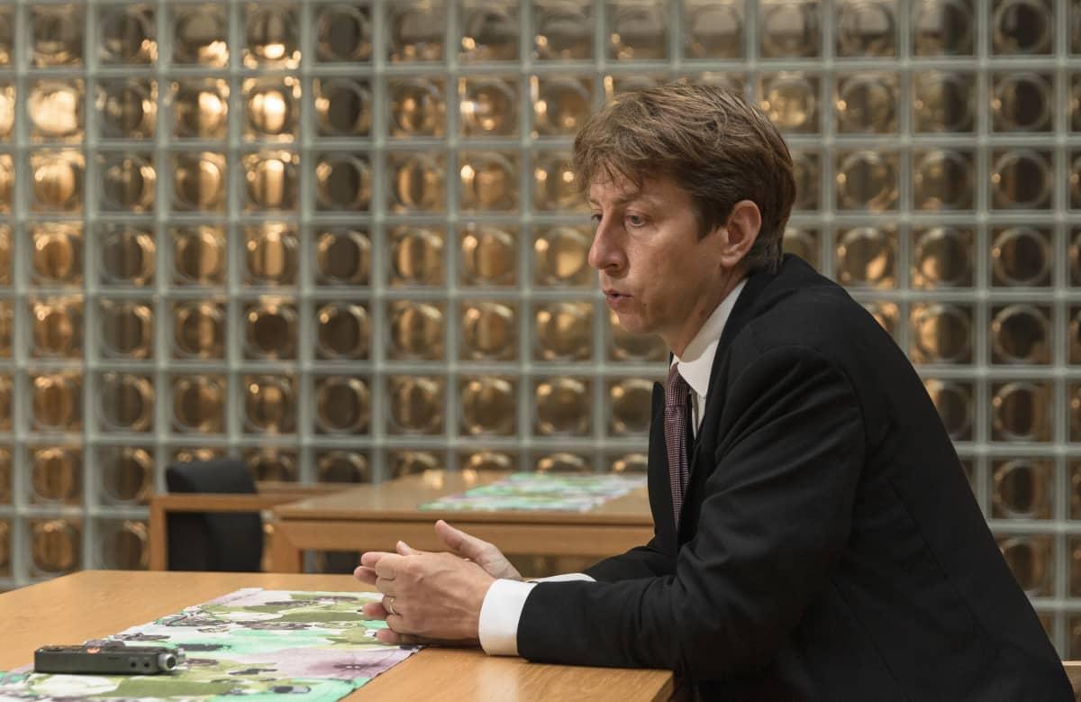 Sakari Puisto istuu pöydän ääressä lasitiiliseinän edessä Eduskunnan Pikkuparlamentin ruokalassa.