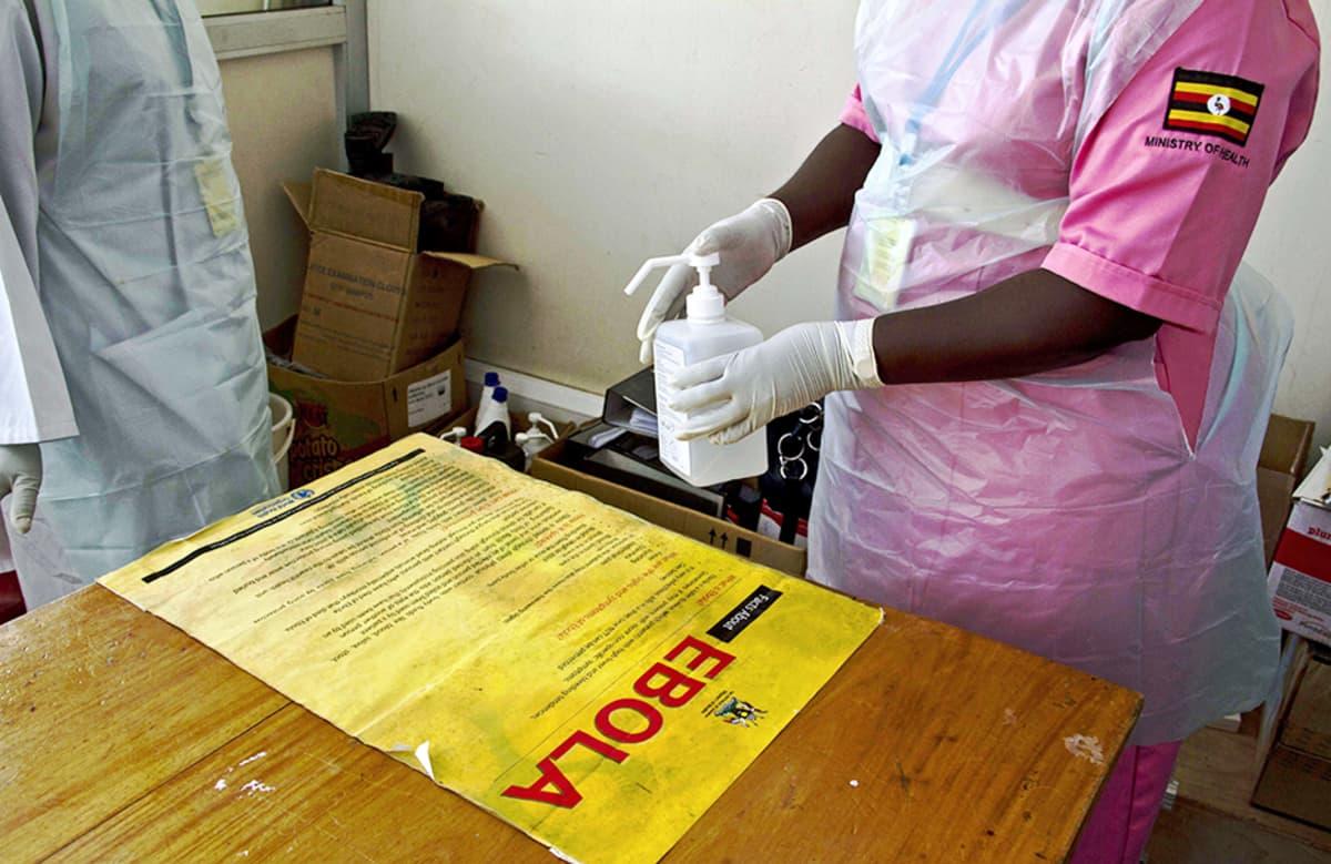 Terveysviranomainen desinfioi pöytää Entebben lentokentällä Ugandassa 8. elokuuta.
