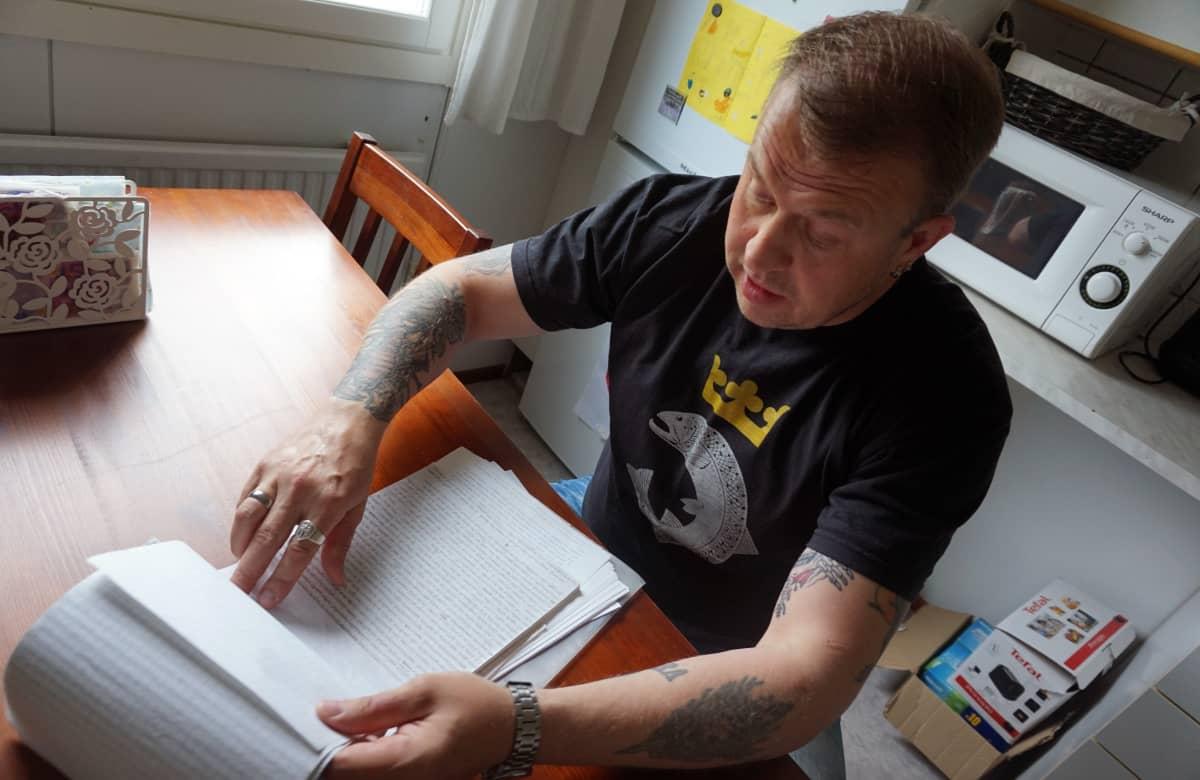 Marko Pesonen istuu pöydän ääressä selaamassa lehtiötä