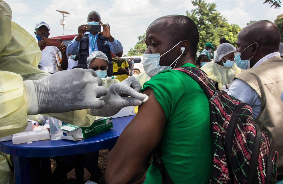 Terveystyöntekijä rokottaa potilasta ulkona.