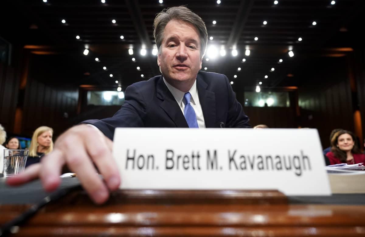 Mies asettelee pöydälle nimikylttiään jossa lukee Hon. Brett M. Kavanaugh