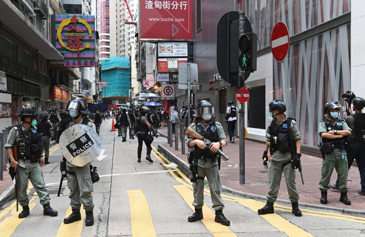 Mellakkavarusteisia poliiseja kadulla.