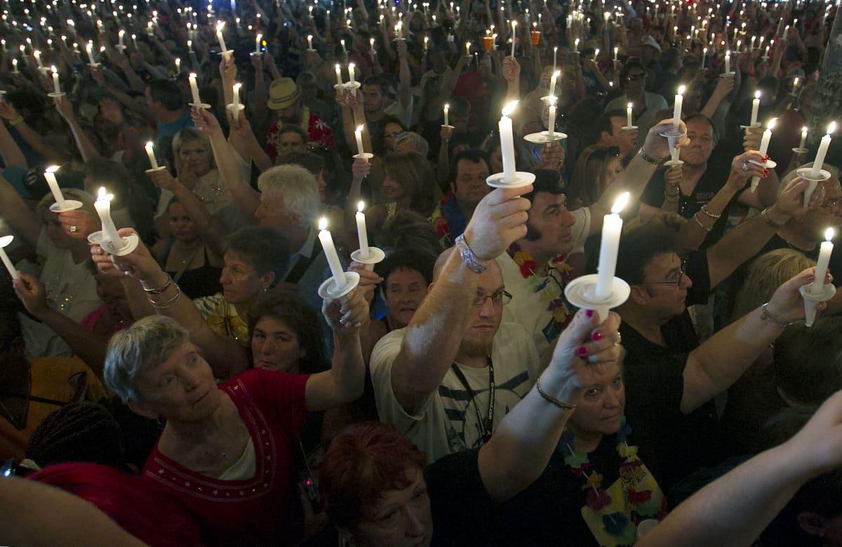 Ihmisiä kynttilät kädessä.