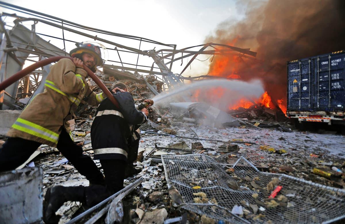 Palomiehet sammuttavat räjähdyksestä aiheutuneita paloja.