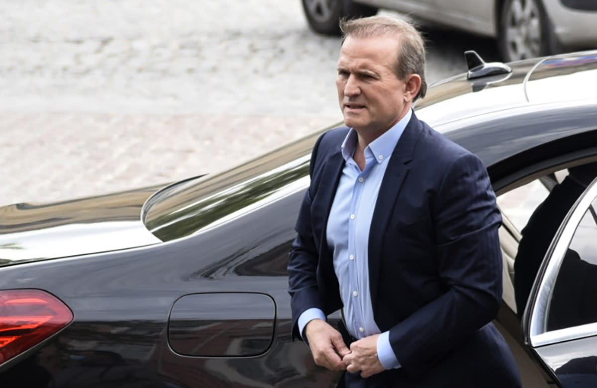 Medvedtšuk  kävelee isolta mustalta autolta tummassa puvussa ja vaaleansinisessä kauluspaidassa ilman kravattia.