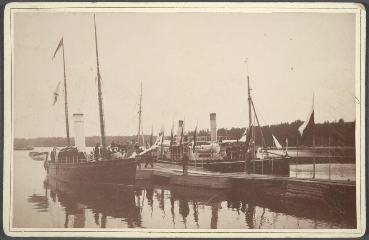 Aleksanteri III kuvassa keskellä astumassa laiturille Lappeenrannassa. Vieressä kaksi isoa purjelaivaa.