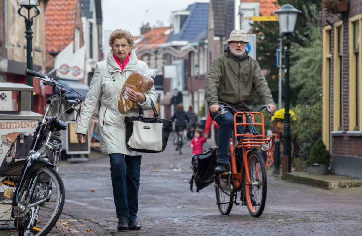 Nainen ja pyöräilevä mies kadulla Texelin kaupungissa Hollannissa.