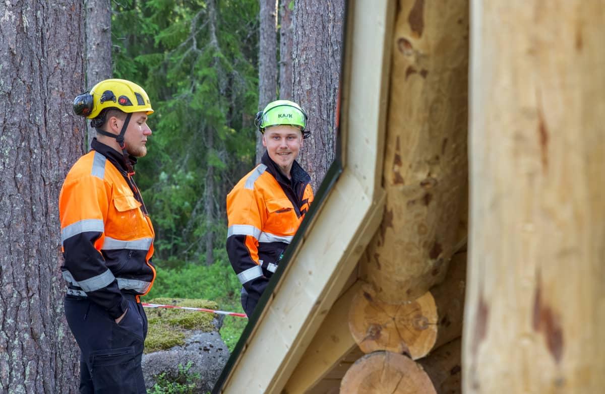 Rakennusmiehet Markus Parviainen ja Sami Laamanen kodan vieressä. Etutalalla kodan seinää.