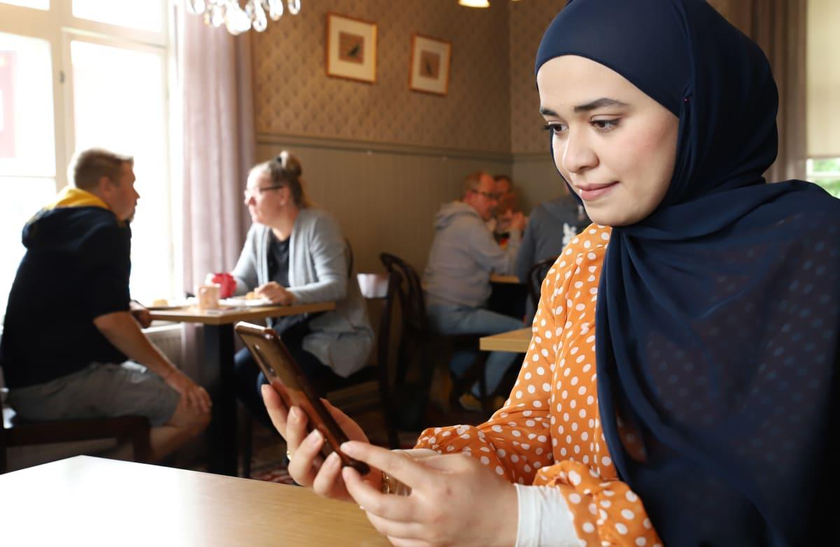 Rand Mohamad Deeb katselee kännykkäänsä Lahtelaisessa kahvilassa