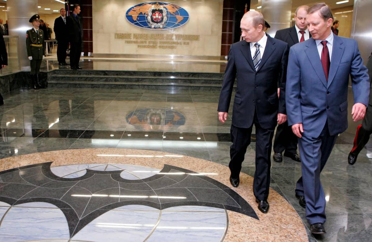 Putin ja Ivanov kävelevät GRU:n rakennuksen aulassa ja katsovat lattiaa, johon on maalattu GRU:n symboli, lepakon kuva.