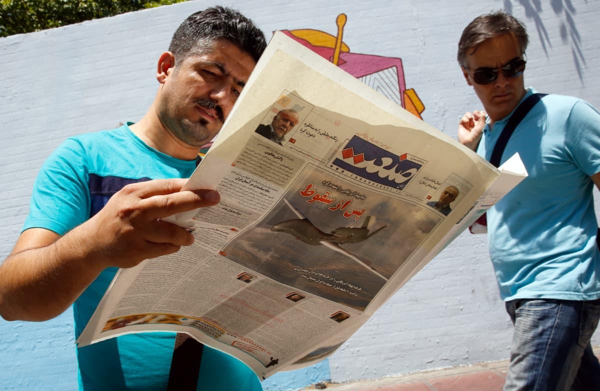 Iranilainen mies lukee Sanaat-lehteä lehtikioskin edessä Teheranissa.