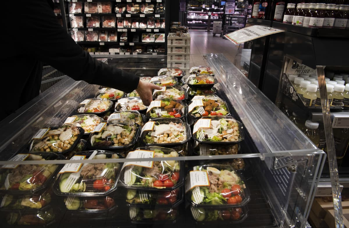 Asiakas ottaa valmiiksi pakatun salaattiannoksen ruokakaupan kylmätiskiltä.