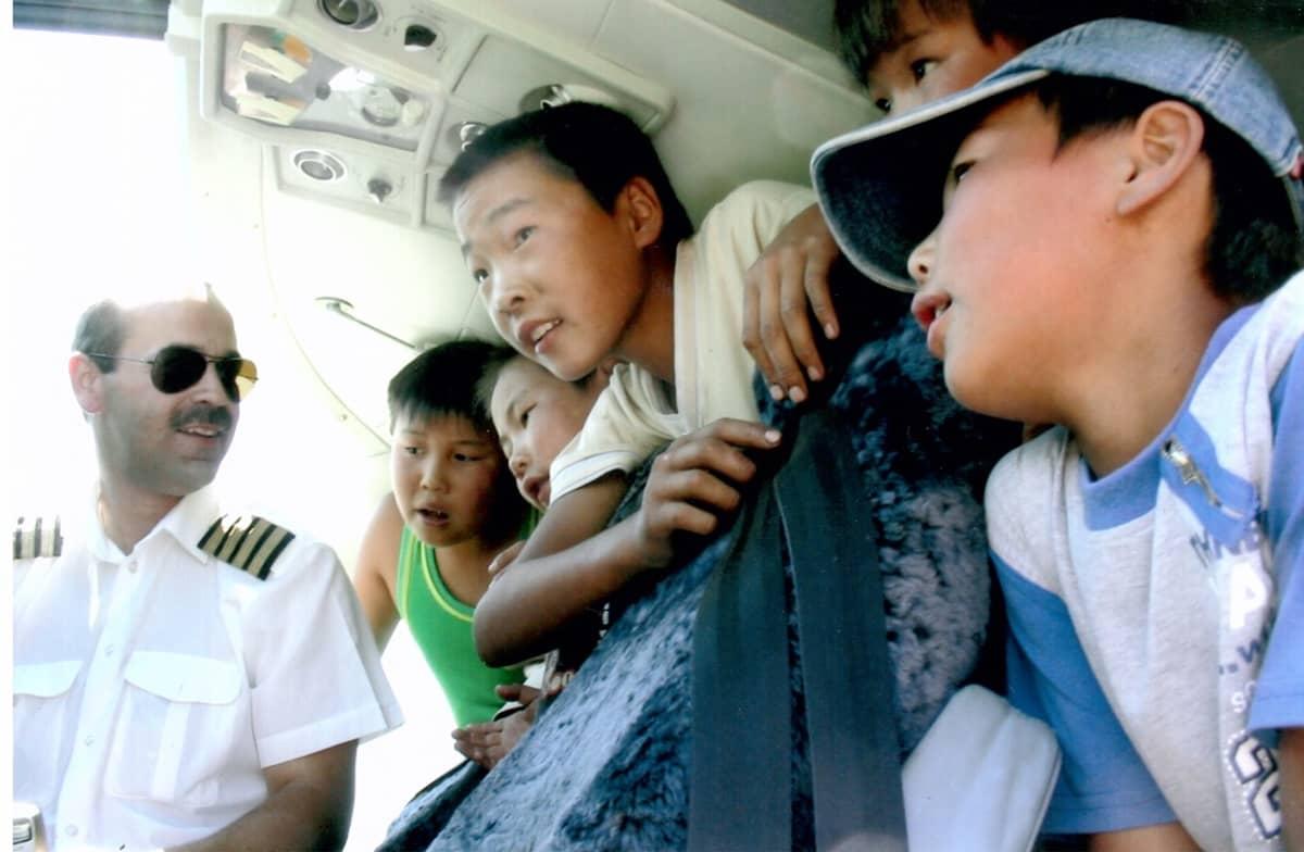 Avustuslentäjä Janne Ropponen Mongoliassa Etelä-Gobin Manlaissa esittelemässä konettaan lapsille lennon tauolla