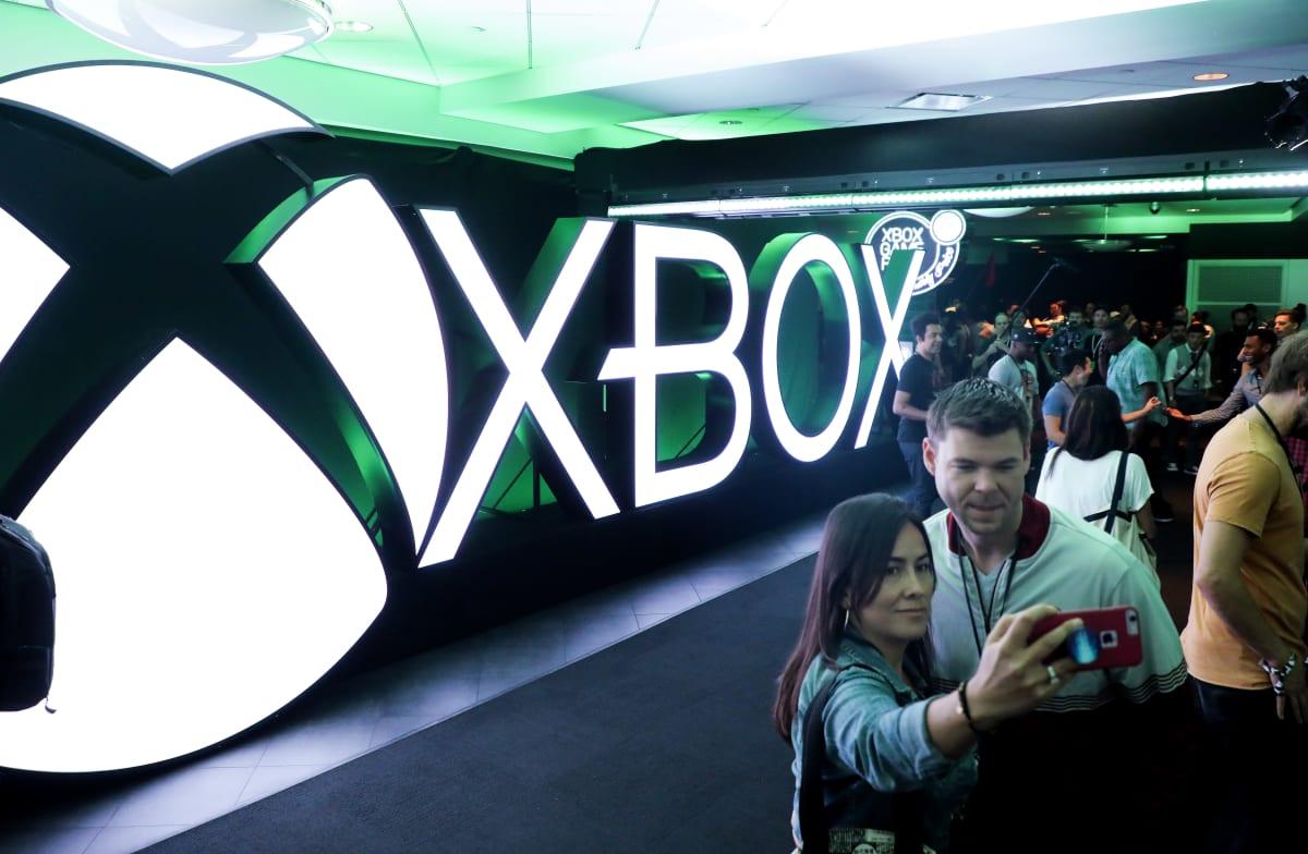 Pariskunta kuvaa itseään Xbox-logon edessä.