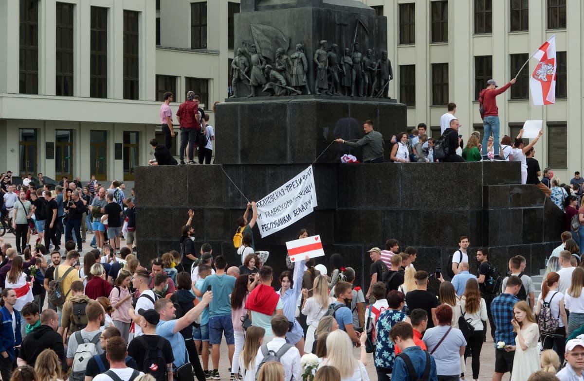 Ihmiset kiipesivät Minskin keskusaukiolla olevan Lenin-muistomerkin päälle.