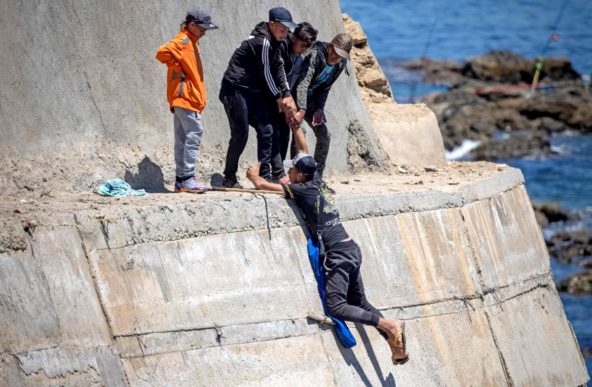 Eurooppaan pyrkivät siirtolaiset kiipeävät rannassa sijaitsevalle muurille.