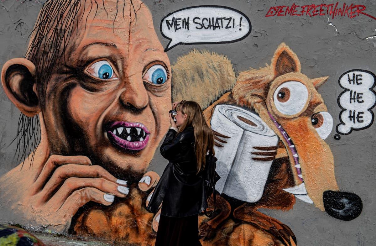 """Nainen ottaa kuvaa Berliinin entiseen muuriin maalatun graffitin edustalla. Kuvassa Taru sormusten herrasta -trilogiasta tuttu Klonkku-hahmo on löytänyt uuden """"aarteen"""" koronakriisin hengessä."""