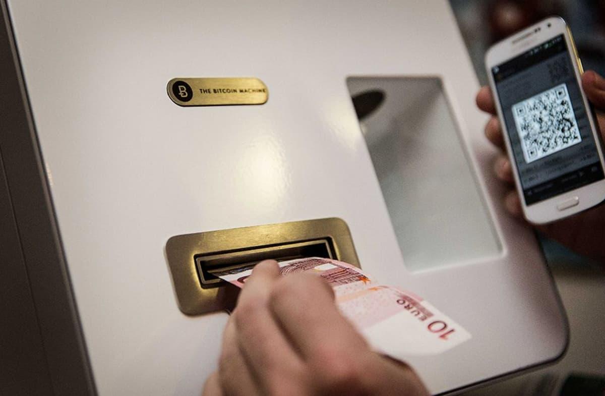 Asiaks vaihtaa käteistä rahaa digirahaksi  bitcoinautomaatilla.