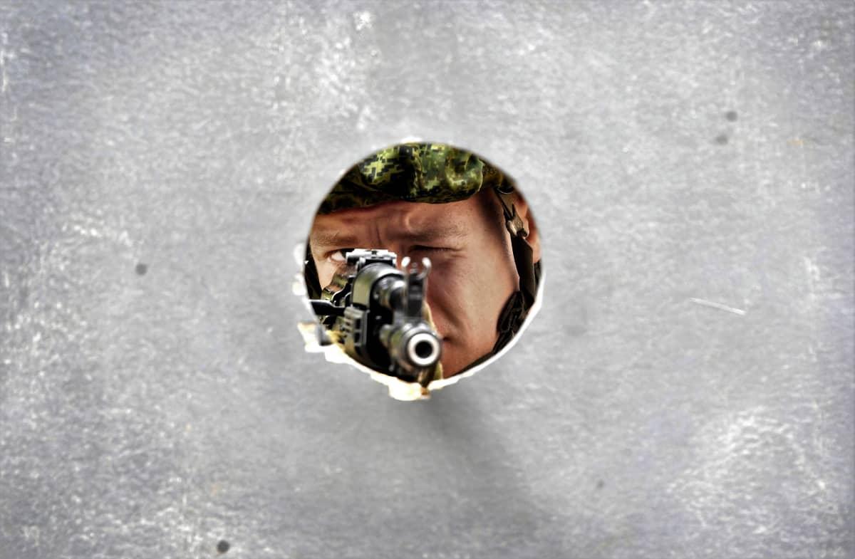 Venäläinen sotilas tähtää rynnäkkökiväärillä seinässä olevan pyöreän aukon läpi.
