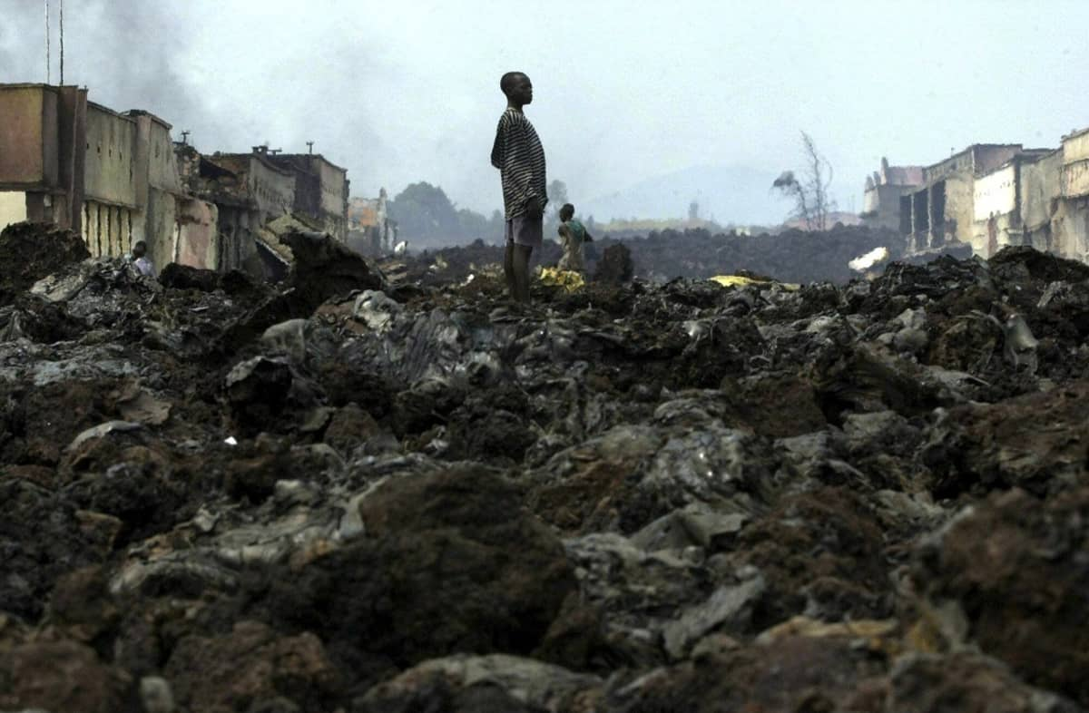 Mustaksi palaneen maiseman keskellä seisoo yksi poika.