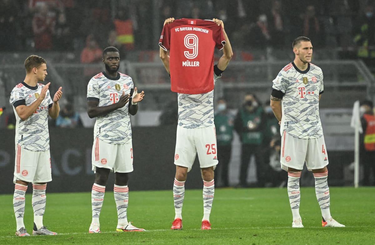 Bayern Münchenin Thomas Müller pitää käsissään sunnuntaina kuolleen Bayernin ja Saksan jalkapallolegenda Gerd Müllerin muistopaitaa hiljaisella hetkellä ennen Supercupin finaalia.