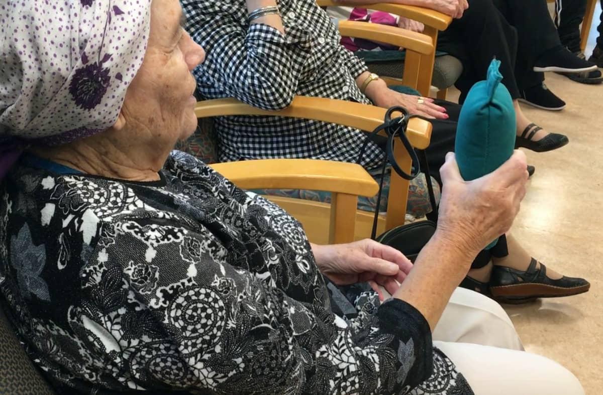 Nainen istuu ja tunnustelee nostelemalla kädessään olevan patukan painoa.