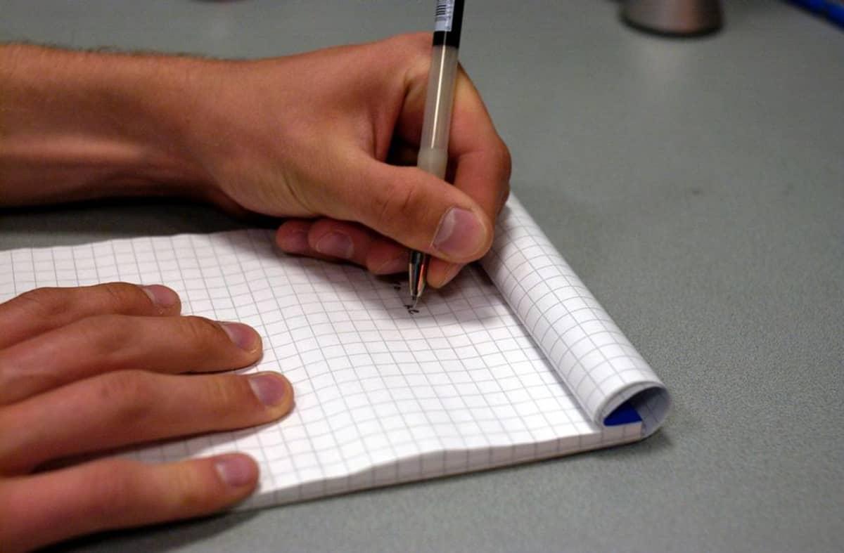 Mies kirjoittaa muistiinpanoja ruutupaperille.