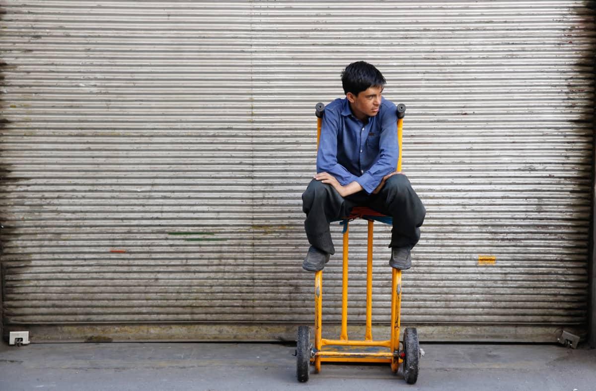 Mies odottaa työtilaisuuksia Teheranin suuressa basaarissa.
