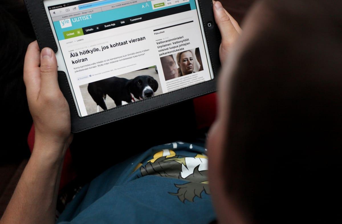 Mies selaa iPadilla uutissivuja.