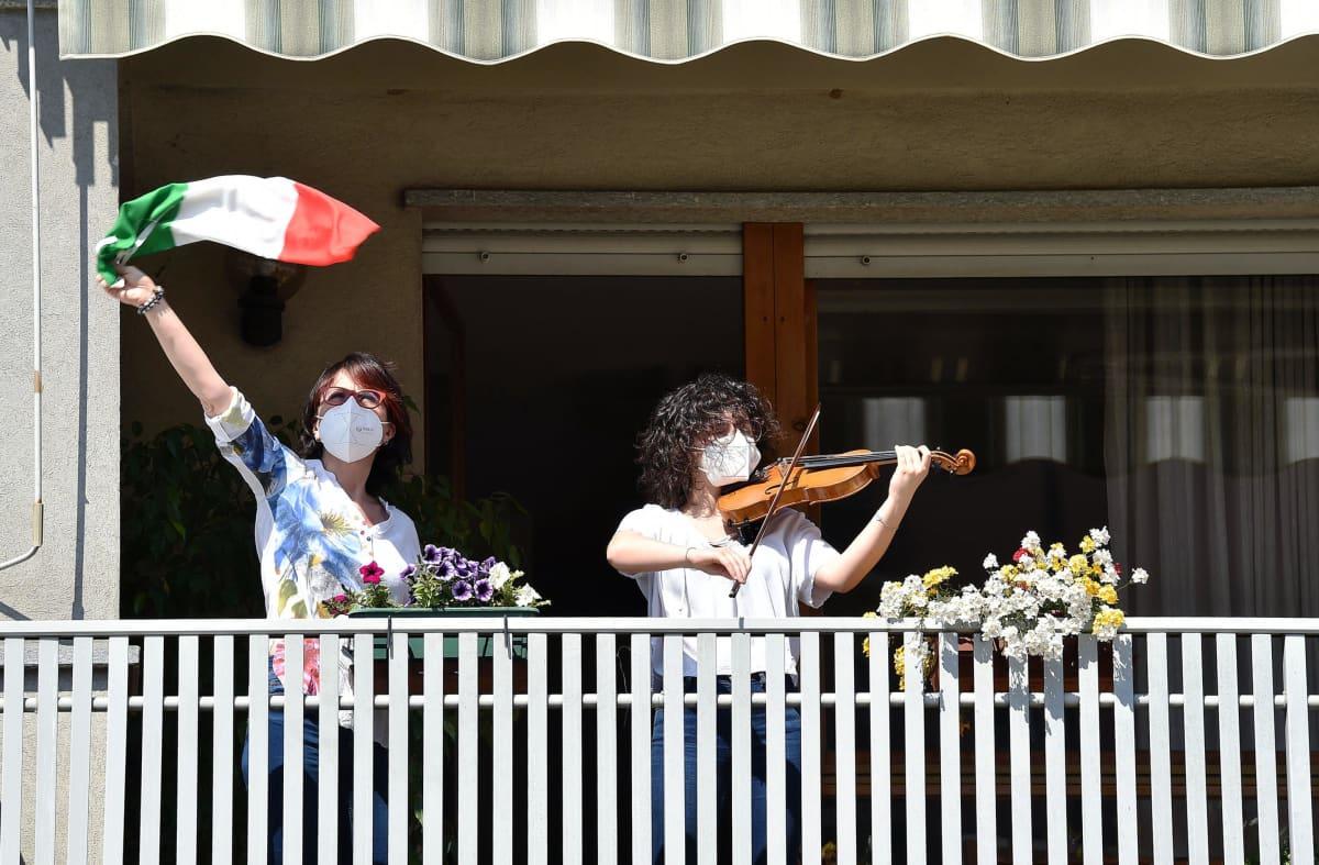 Nainen soittaa kasvomaskissa viulua parvekkeella, toinen nainen heiluttaa Italian lippua vieressä.
