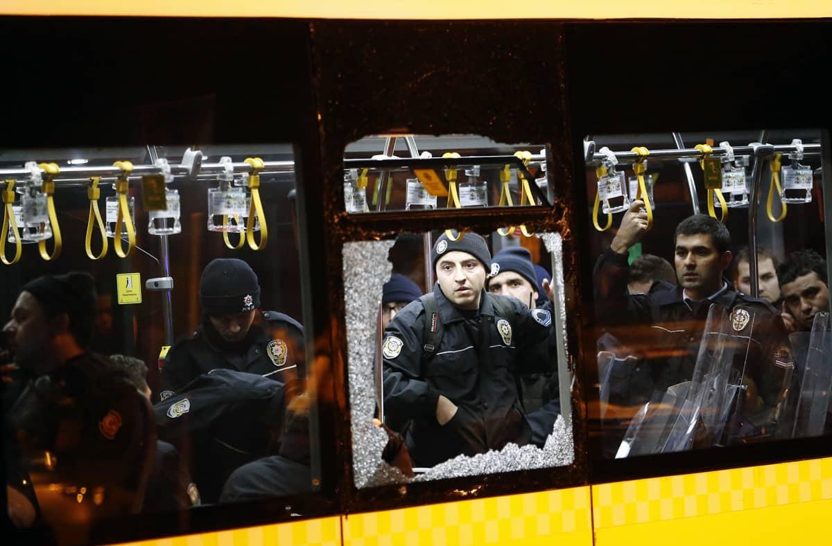 Poliisit seisovat pommi-iskussa vaurioituneen bussin sisällä Istanbulissa.