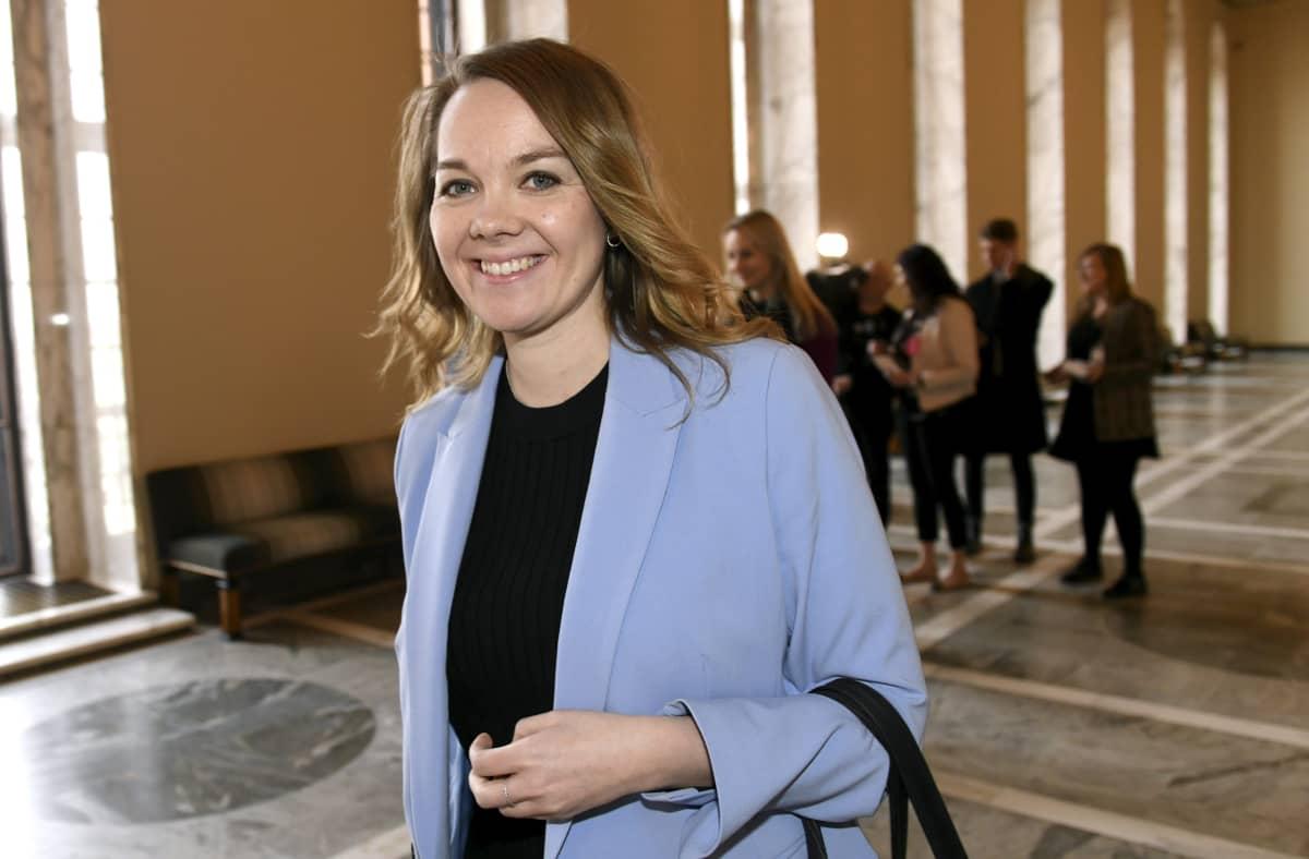 Katri Kulmuni kuvattuna eduskunnassa. Kuvassa Kulmunilla on vaaleansininen jakku ja hän hymyilee.